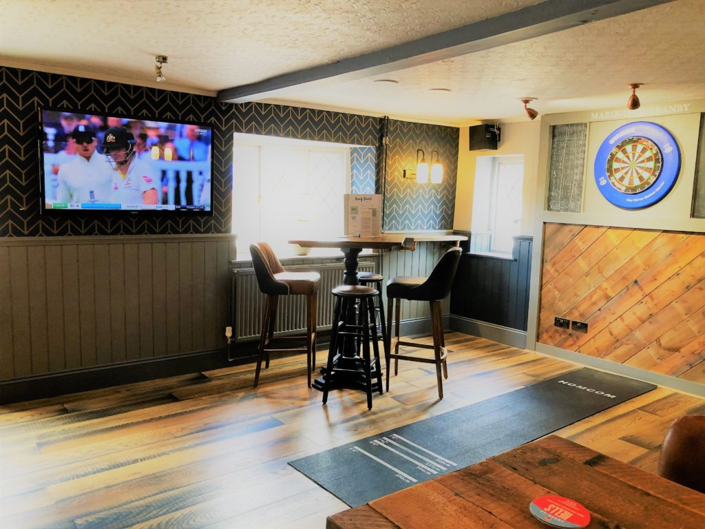 large screen tv with sky sports bt sports seating and dartboard at the marquis of granby pub stevenage